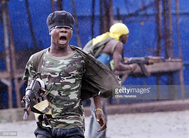 A government militia soldier screams after firing at rebel troops July 25 2003 at a key bridge in Monrovia Liberia The standoff at Monrovia's bridges...