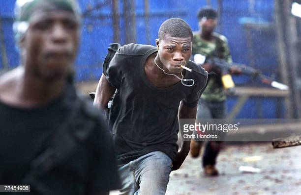 Government militia soldiers duck from incoming rebel fire July 25 2003 at a key bridge in Monrovia Liberia The standoff at Monrovia's bridges...