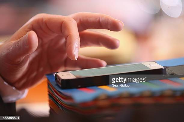 A government minister taps on an Apple iPhone smartphone prior to the weekly German government cabinet meeting on April 8 2014 in Berlin Germany High...