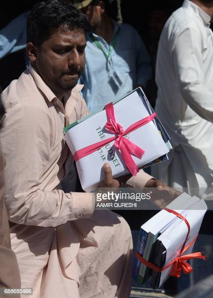 A government official offloads bundles of budget documents to the parliament where Pakistani Finance Minister Ishaq Dar presented the national budget...