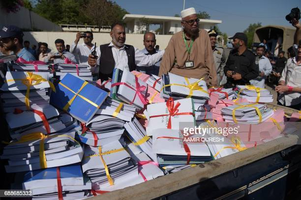 Government officials escort a vehicle carrying bundles of budget documents to the parliament where Pakistani Finance Minister Ishaq Dar presented the...