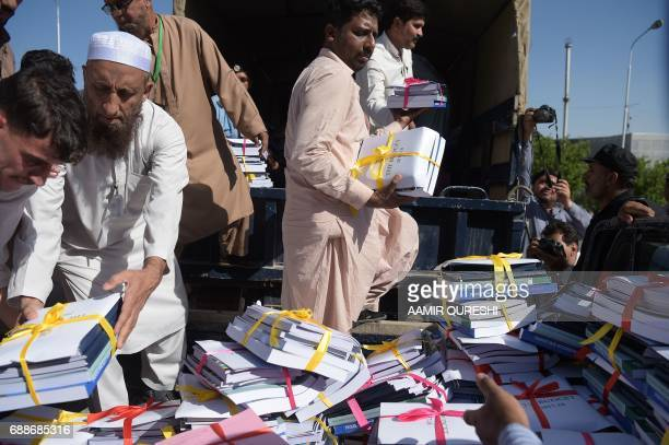 Government officials offload bundles of budget documents to the parliament where Pakistani Finance Minister Ishaq Dar presented the national budget...
