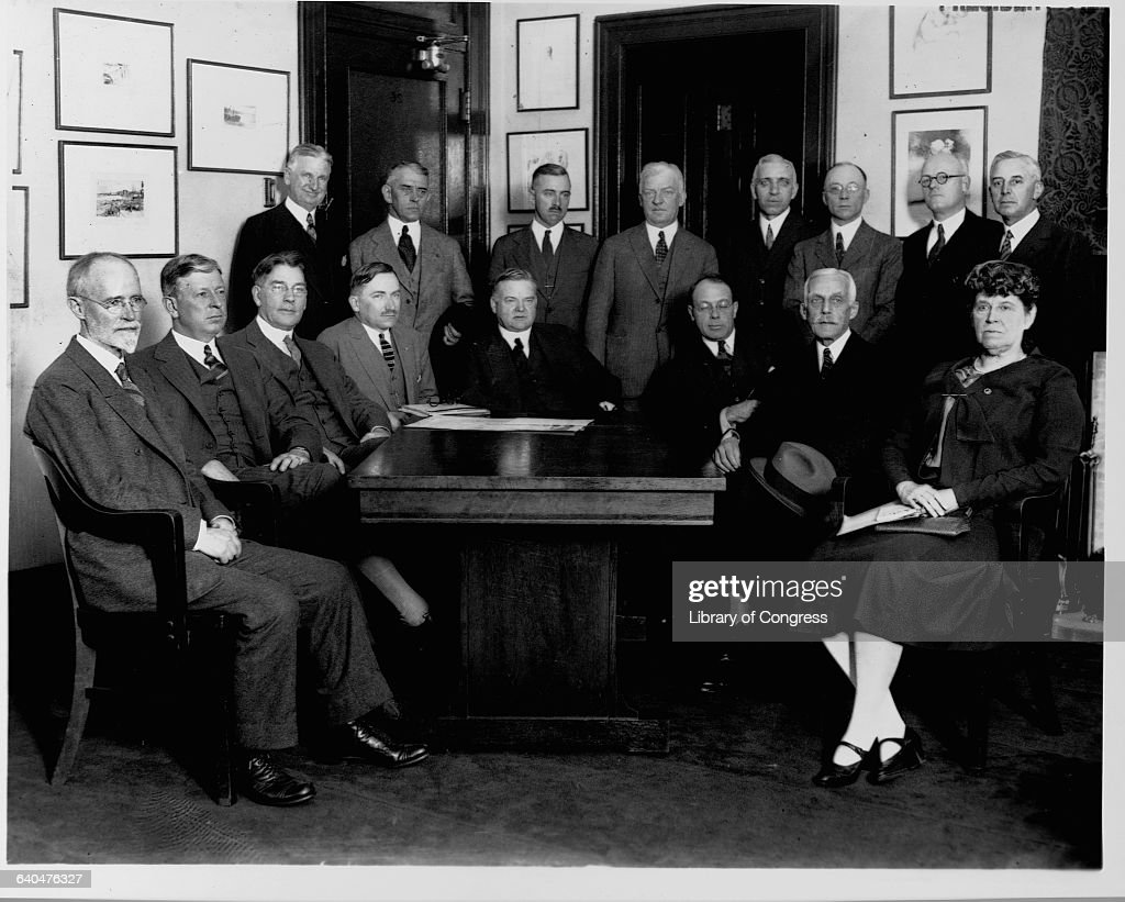 Government representatives, including cabinet members Dwight F. Davis, Curtis Wilbur, Herbert Hoover, and Andrew W. Mellon, meet with Red Cross workers to discuss flood relief for the Mississippi River valley.