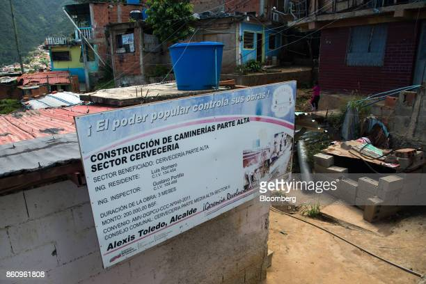 A government sign is displayed informing residents of the construction of new sidewalks in La Guaira Venezuela on Friday Oct 6 2017 As Venezuela...