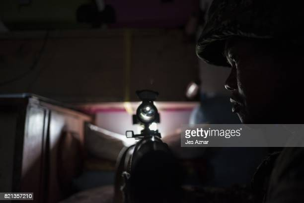 A government sniper adjusting his rifle as he takes position inside a house on July 22 2017 in Marawi southern Philippines The Philippine Congress...