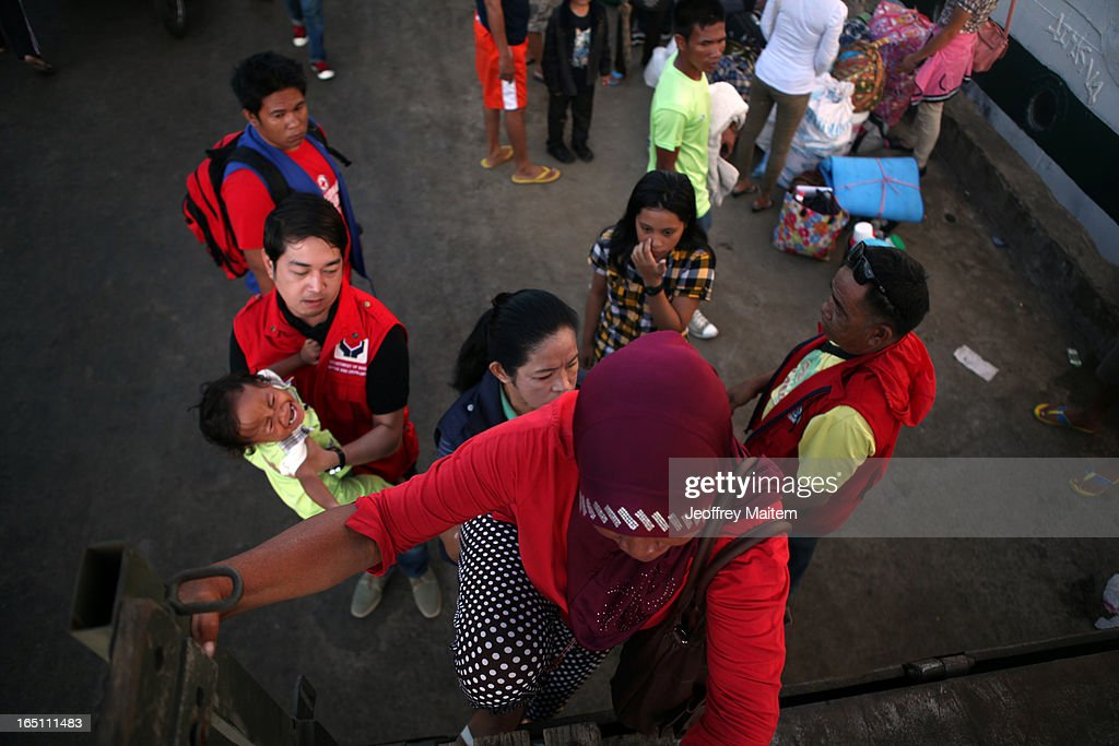 A government social welfare officer carries a child displaced by continuing armed conflict between the supporters of Philippine Muslim clan Sulu Sultan Jamalul Kiram III and Royal Malaysian Police in Sabah, Malaysia, as they arrive on March 30, 2013 in Bonggao, Tawi-Tawi, Philippines. Following the insurgency in Sabah and the Malaysian government's subsequent crackdown on undocumented Filipinos, over 4000 people, mostly Filipino Muslims, have begun evacuating to the southern provinces of Basilan, Sulu, and Tawi-Tawi in the Philippines, with numbers expected to reach more than 100,000.