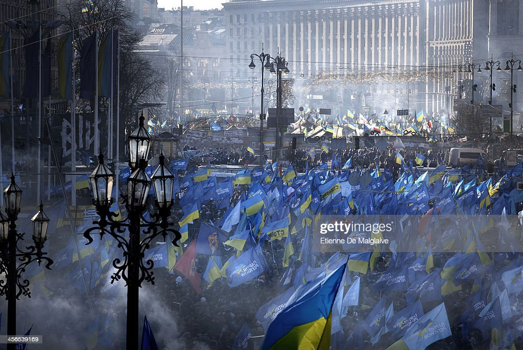Government supporters stage a demonstration on Europe Square, a stone's throw away from Independance Square barricades (background) occupied by protesters, son December 14, 2013 in Kiev, Ukraine. The anti-government protesters are demanding the resignation of the government after Ukrainian President Victor Yanukhovych angered many by refusing to sign an agreement that would strengthen cooperation with the European Union and instead keep ties with Russia.