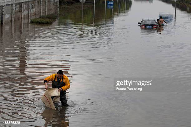 A government worker works on the sewage as two men push a car back from a flooded road on April 07 2015 in Changsha China Downpours in April have...