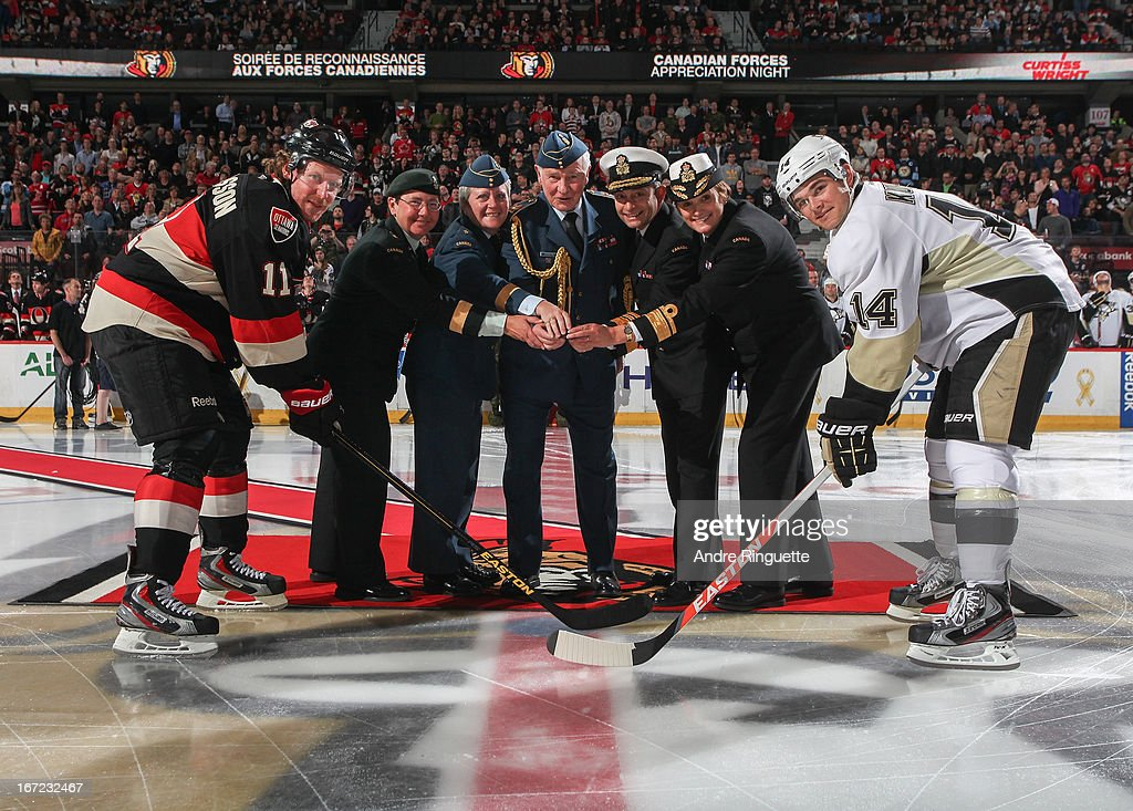 Governor General David Johnson (center) drops the puck for a ceremonial face-off with <a gi-track='captionPersonalityLinkClicked' href=/galleries/search?phrase=Daniel+Alfredsson&family=editorial&specificpeople=201853 ng-click='$event.stopPropagation()'>Daniel Alfredsson</a> #11 of the Ottawa Senators and <a gi-track='captionPersonalityLinkClicked' href=/galleries/search?phrase=Chris+Kunitz&family=editorial&specificpeople=604159 ng-click='$event.stopPropagation()'>Chris Kunitz</a> #14 of the Pittsburgh Penguins on Canadian Forces Appreciation Night on April 22, 2013 at Scotiabank Place in Ottawa, Ontario, Canada.