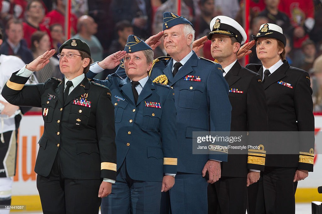 Governor General of Canada David Johnson (center) salutes during the singing of the national anthems on Canadian Forces Appreciation Night, prior to a game between the Ottawa Senators and the Pittsburgh Penguins, at Scotiabank Place, on April 22, 2013 in Ottawa, Ontario, Canada.