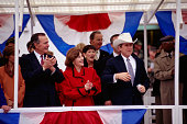 Governor George W Bush wearing a cowboy hat with wife Laura Bush and father George Bush during inauguration