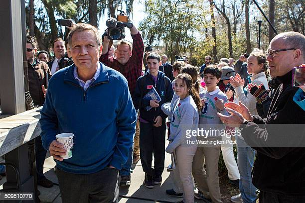 Governor John Kasich is applauded by his supporters as he walks up to Finn's Brick Oven for his Townhall Wednesday Feb 10 2016 in Mount Pleasant