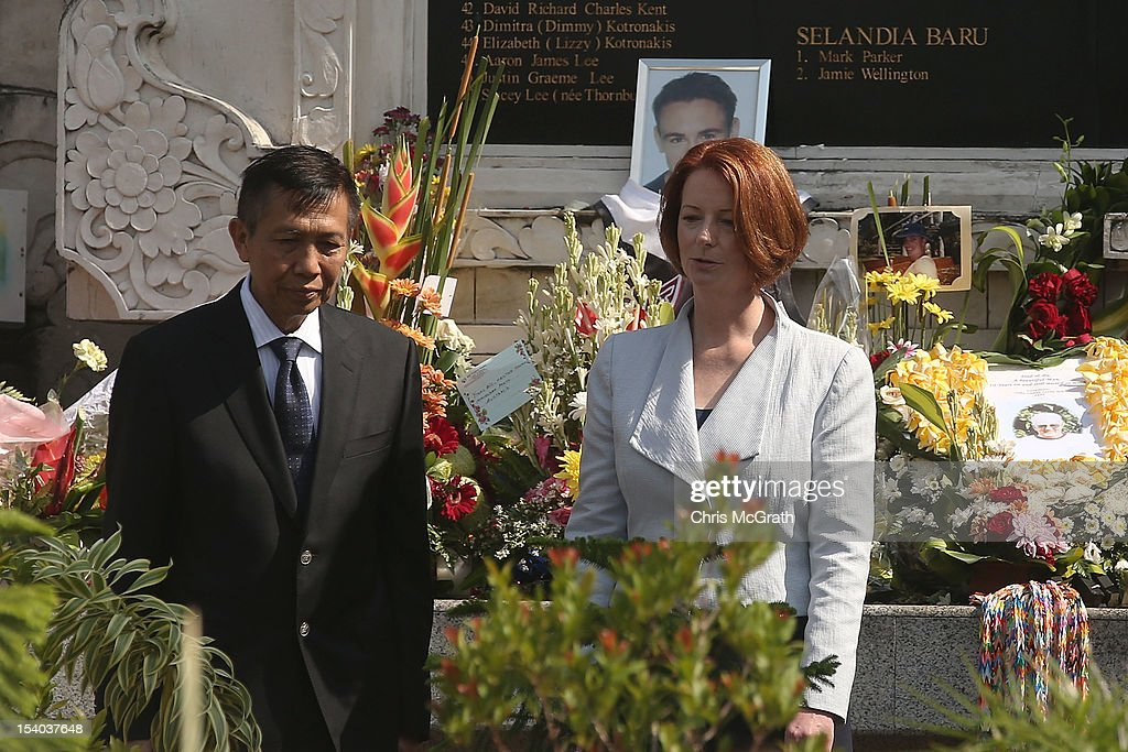 Governor of Bali, I Made Mangku Pastika (L) and Australian Prime Minister <a gi-track='captionPersonalityLinkClicked' href=/galleries/search?phrase=Julia+Gillard&family=editorial&specificpeople=787281 ng-click='$event.stopPropagation()'>Julia Gillard</a> pay their respects to those who were killed during a visit to the Bali Bombing Memorial at Jalan Legian, Bali, on October 13, 2012 in Indonesia. The Prime Ministers visit brings to a close the official 10th anniversary ceremonies for the families of those killed in the 2002 Kuta bombings which killed 202 people including 88 Australians.