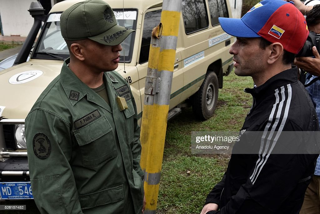 Governor of Miranda state Henrique Capriles (R) talks with a military officer asking permision to visit jailed opposition Leader Leopoldo Lopez on his 45th Birthday in Los Teques, Venezuela on April 29, 2016.