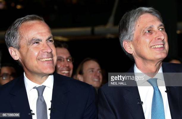 Governor of the Bank of England Mark Carney and Britain's Chancellor of the Exchequer Philip Hammond gesture during the International Fintech...
