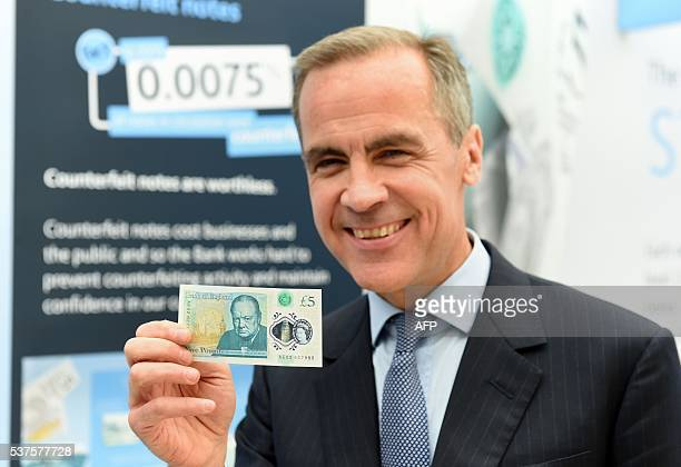 Governor of the Bank of England Mark Carney poses with the new £5 banknote bearing the image of wartime leader Winston Churchill at its unveiling by...