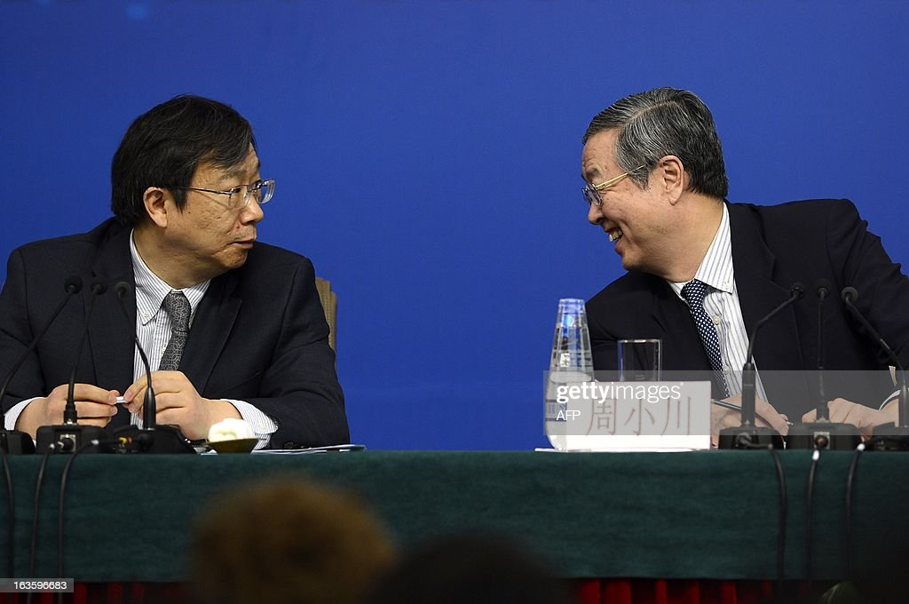 Governor of the People's Bank of China, Zhou Xiaochuan (R) chats with Yi Gang(L), Director of the State Administration of Foreign Exchange during a press conference in the first session of the 12th National People's Congress (NPC) in Beijing on March 13, 2013. Thousands of delegates from across China meet this week to seal a power transfer to new leaders whose first months running the Communist Party have pumped up expectations with a deluge of propaganda.