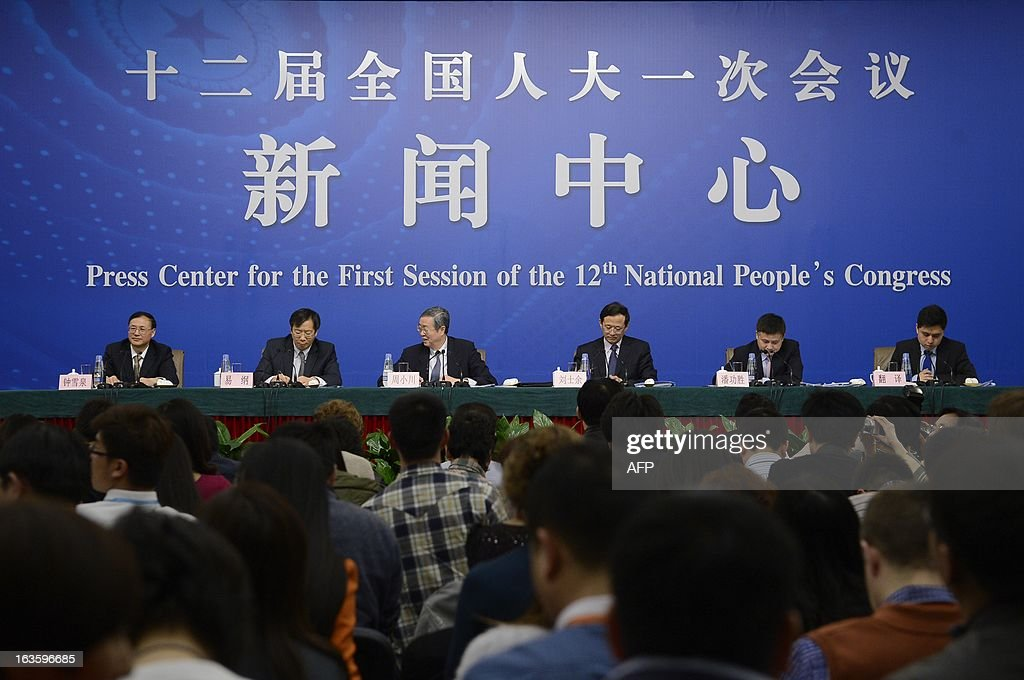 Governor of the People's Bank of China, Zhou Xiaochuan (3L) reacts during a press conference in the first session of the 12th National People's Congress (NPC) in Beijing on March 13, 2013. Thousands of delegates from across China meet this week to seal a power transfer to new leaders whose first months running the Communist Party have pumped up expectations with a deluge of propaganda. AFP PHOTO / WANG ZHAO