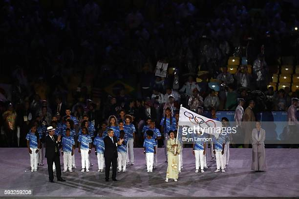 Governor of Tokyo Yuriko Koike waves the IOC flag while IOC President Thomas Bach and the Mayor of Rio de Janeiro Eduardo Paes watch on stage at the...