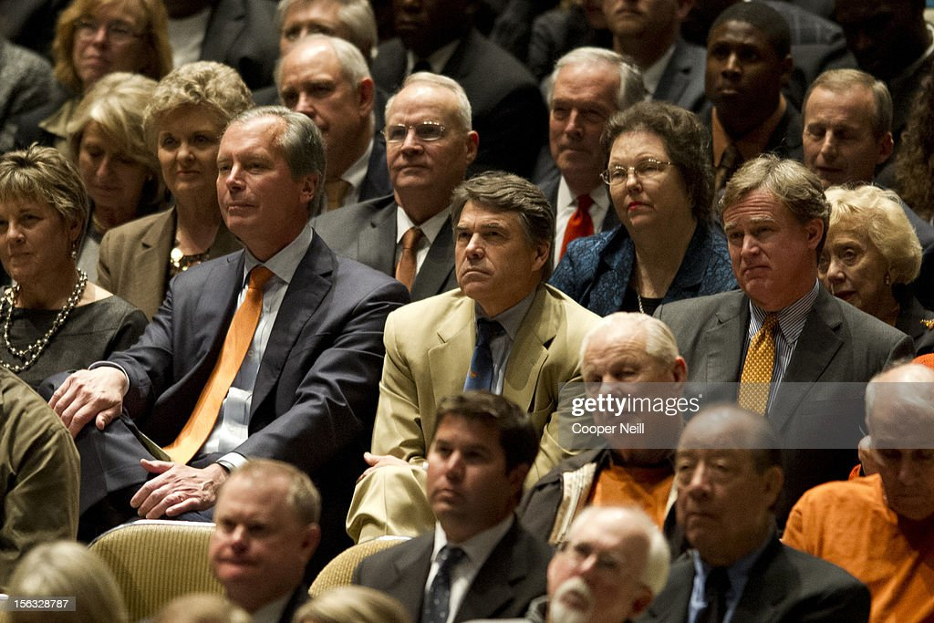 Governor Rick Perry sits next to Lt. Govenor David Dewhurst during a memorial service for former University of Texas Longhorns head coach Darrell K Royal on November 13, 2012 at the Frank Erwin Center in Austin, Texas.