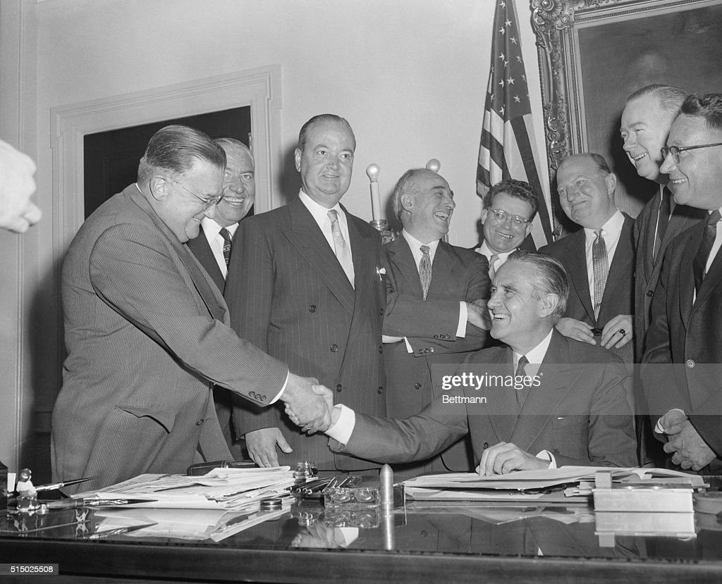 Governor W. Averell Harriman of New York shakes hands with Walter O'Malley, the Brooklyn Dodgers' president, after the governor today signed the bill authorizing construction of a sports center in Brooklyn - a center that would include a new home for the Brooklyn Dodgers. Mr. O'Malley; Joseph Sharkey, vice chairman of the City Council; John Cashmore, Brooklyn borough president in whose office the signing ceremony took place; Robert Moses, New York City Park Commissioner, and Governor Harriman.