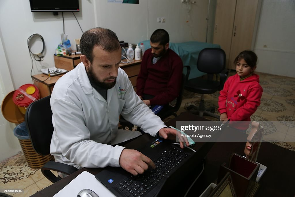 Gozyasi Nasir (R), daughter of Mamun Halid Nasir (C), 27, who lost his legs, right hand fingers, eyes and hearing in an barrel bomb attack carried out by the war crafts belonging to Assad Regime Forces in Idlib, is seen as a doctor examines her father at a hospital in Hatay, Turkey on February 11, 2016. Mamun Halid Nasir gained his sight again after IHH Humanitarian Relief Foundation paid surgery expenses.