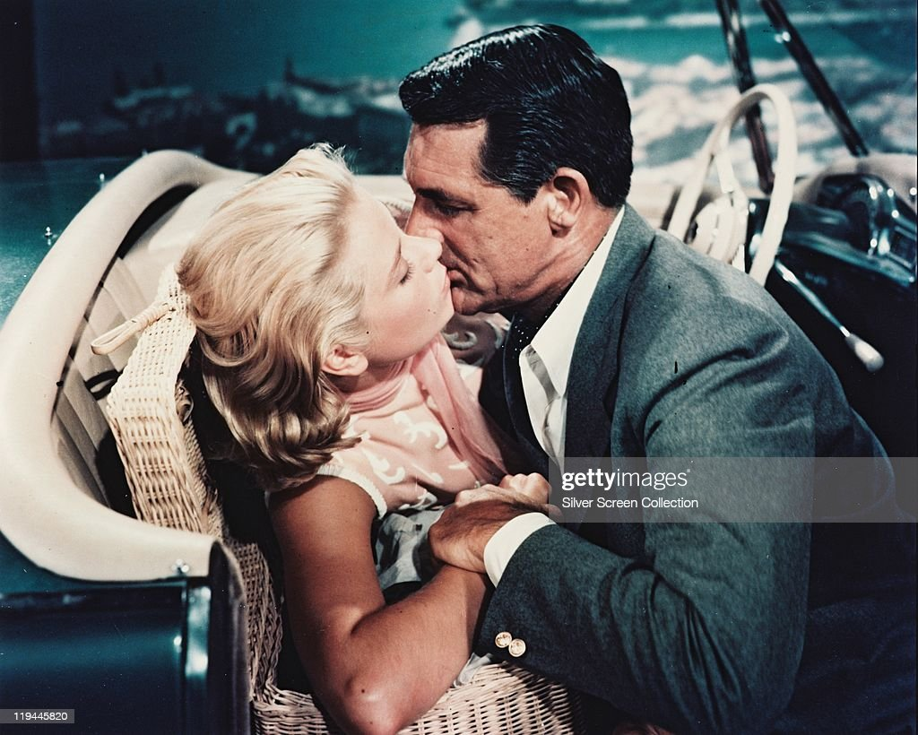Grace Kelly (1929–1982) and Cary Grant (1904–1986) kissing in the front seat of a car in a publicity still issued for the film, 'To Catch a Thief', 1955. The 1955 film, directed by Alfred Hitchcock (1899–1980), starred Kelly as 'Frances Stevens', and Grant as 'John Robie'.