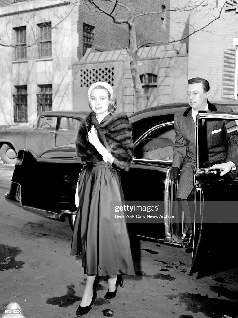 Grace Kelly, clad in a mink stole and topped off with a pink straw turban, arrives for Rita Gam wedding.