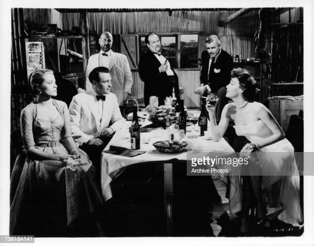 Grace Kelly Clark Gable Ava Gardner and others sit around a table drinking wine in a scene from the film 'Mogambo' 1953