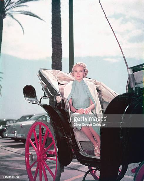Grace Kelly US actress wearing a blue dress with a white cardigan draped over her shoulders as she rides in a horsedrawn carriage 1955