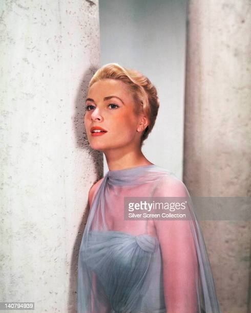 Grace Kelly US actress wearing a blue gown with blue sheer fabric wrap in a studio portrait circa 1955