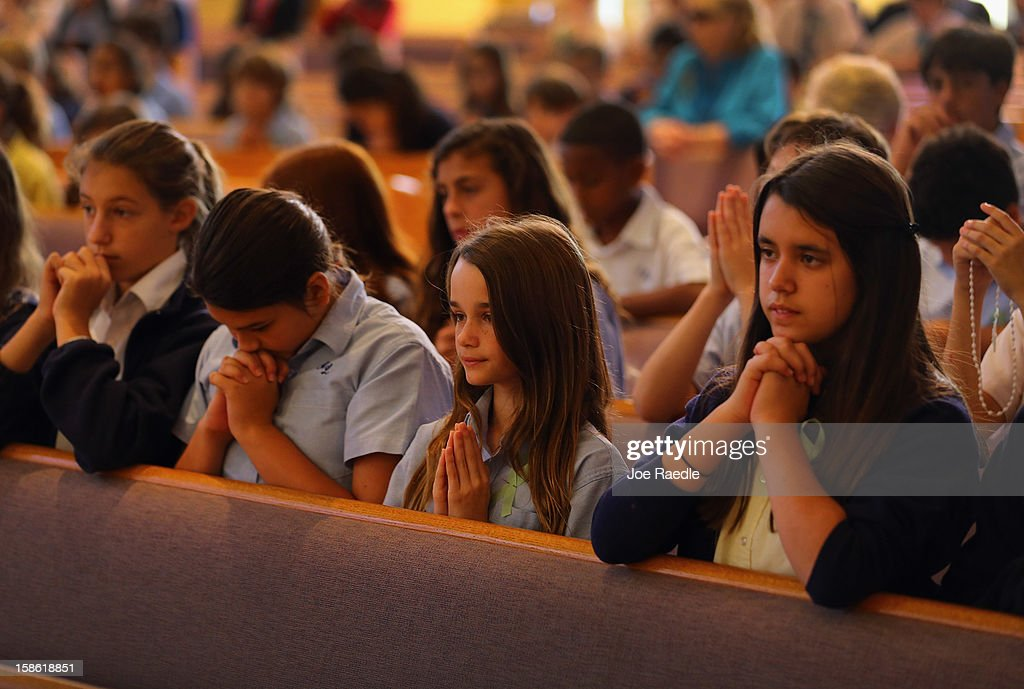 Grace Romanik, Jenny Rotondo and Victoria Gonzalez (2nd L-R) pray during a service, at St. Rose of Lima School, for the victims of the school shooting one week ago in Newtown, Connecticut on December 21, 2012 in Miami, Florida. Across the country people marked the one week point since the shooting at Sandy Hook Elementary School in Newtown, Connecticut that killed 26 people.