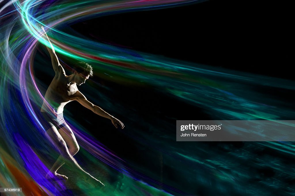 graceful dancer in swirl of colored light effect : Stock Photo