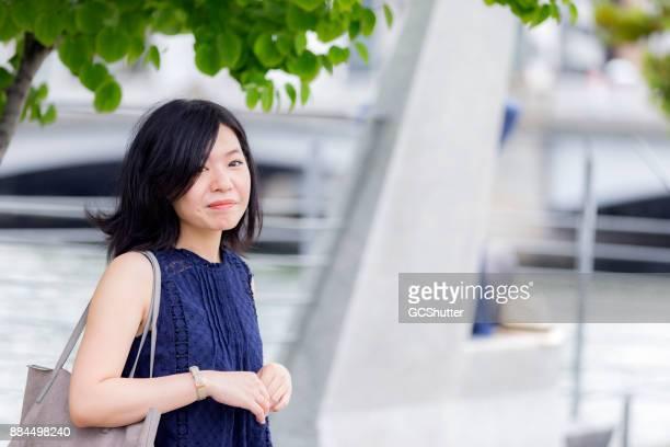 カメラを見て彼女のショルダー バッグで優雅な日本の女の子