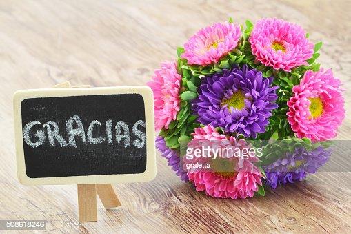 Gracias (thank you in Spanish) written on blackboard, colorful bouquet : Stock Photo
