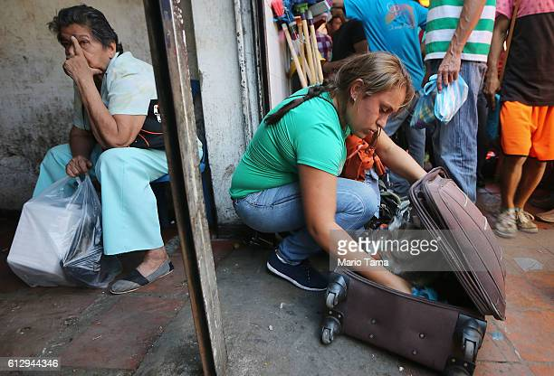 Gracy from Venezuela packs food she purchased into a suitcase after travelling 14 hours from her town to cross the border into Colombia on October 4...