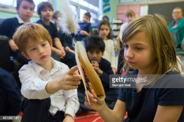 TORONTO ON NOVEMBER 21 Grade 3 students Henry Keating and Finnia O'Neill DiMascio at Vincent de Paul School look at red tailed hawk feathers during a...