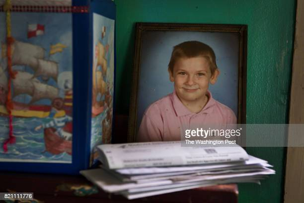 A gradeschool photo of Tyler McGloghlin next to a stack of bills in the home that he shares with his mother Sheila McGlothlin in Grundy VA on May 26...