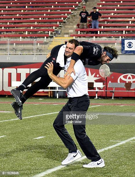 Graduate assistant coach Ben Cotton of the UNLV Rebels picks up and spins quarterback Dalton Sneed of the Rebels on the field after the team's 4520...