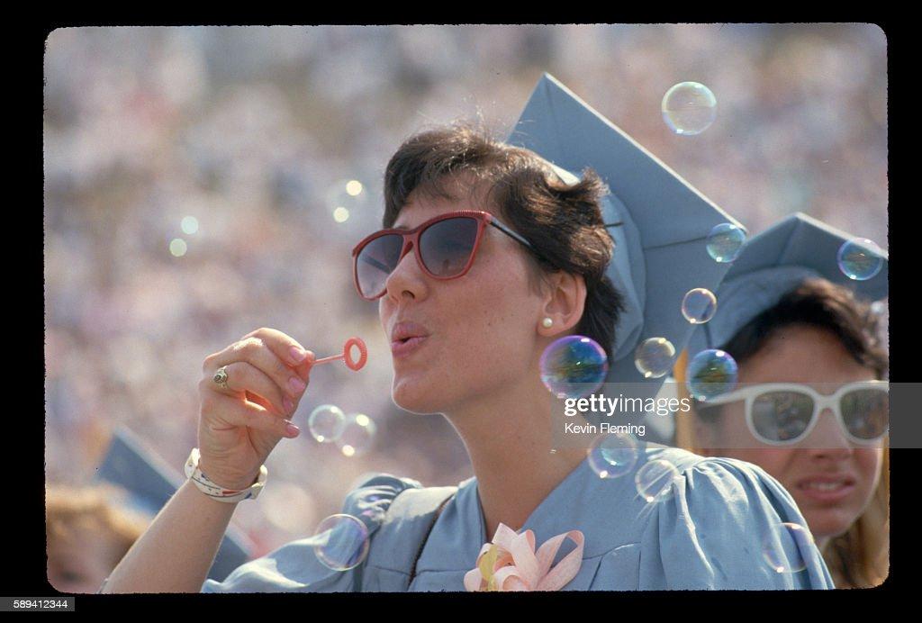A graduate blows soap bubbles at a graduation ceremony at the University of Delaware Newark Delware