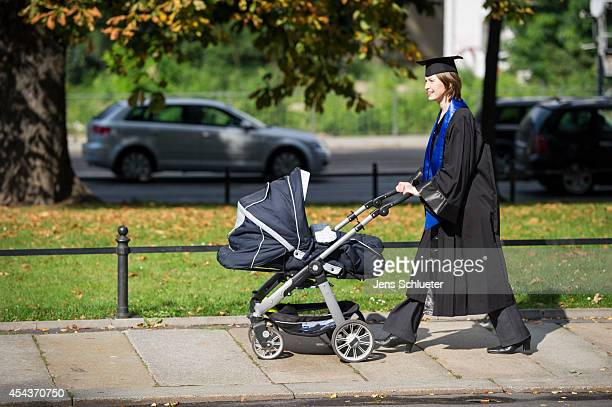 Graduate in gown and caps push after their graduation at the HHL Leipzig Graduate School of Management a baby carriage on August 30 2014 in Leipzig...