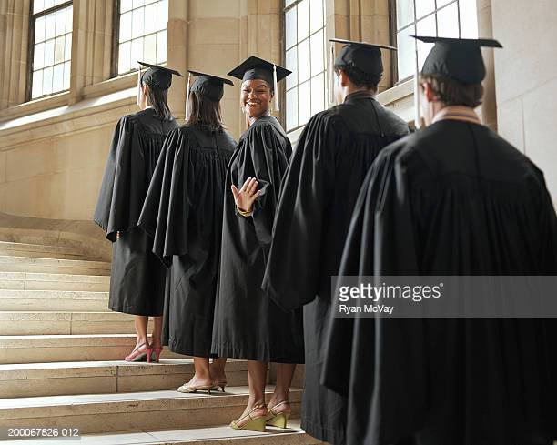 Graduate in line climbing stairs, turning to wave