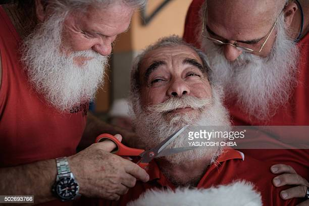 TOPSHOT A graduate of the Brazil's School of Santa Claus gets his beard trimmed by students in Rio de Janeiro Brazil on December 28 2015 The school...
