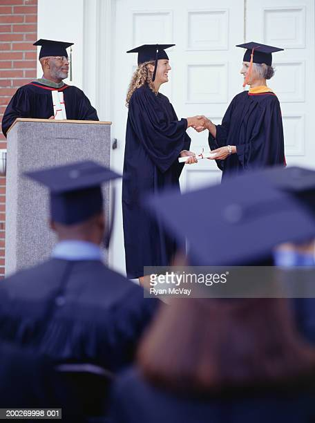 Graduate receiving diploma at graduation ceremony