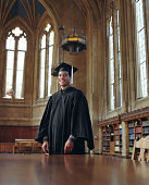 Graduate standing in reading room of library, portrait