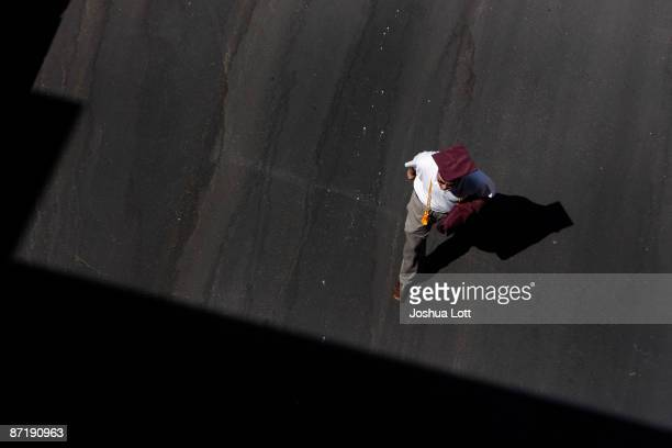A graduate student walks with his cap and gown before the start of the Arizona State University graduation at Sun Devil Stadium May 13 in Tempe...