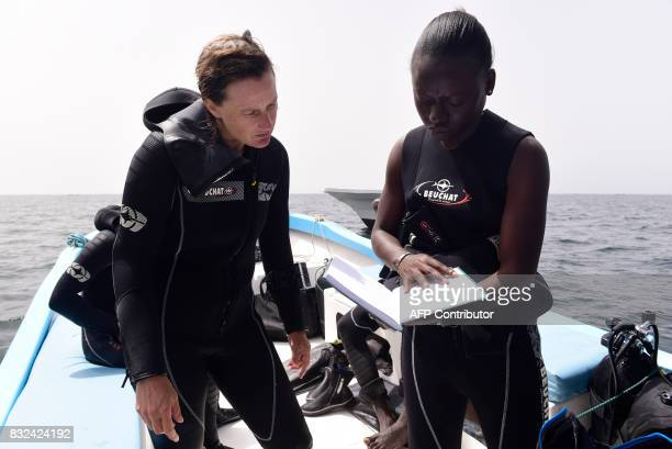 Graduate students from Dakar's Chiekh Anta Diop university work on datas on a boat during a diving expedition to find traces of slave shipwrecks on...