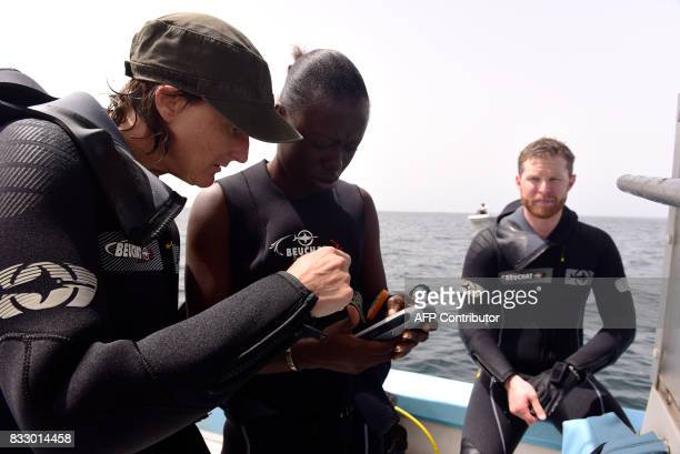 Graduate students from Dakar's Chiekh Anta Diop university work on data on a boat during a diving expedition to find traces of slave shipwrecks on...