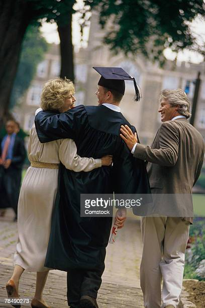 Graduate walking with parents
