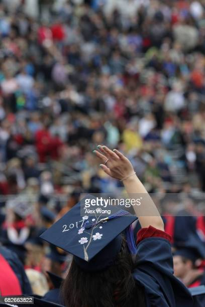 A graduate waves during a commencement at Liberty University May 13 2017 in Lynchburg Virginia President Donald Trump is the first sitting president...